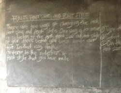 A classroom in rural Ghana where a teacher had written instructions for changing a computer font on the blackboard.